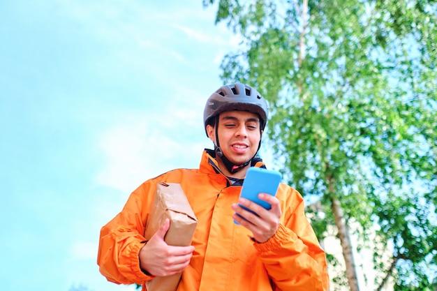 라티노 자전거 배달원이 스마트 폰을 사용하여 패키지를 배달합니다.