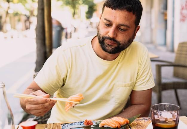 Латиноамериканский мальчик в желтой футболке ест японскую еду