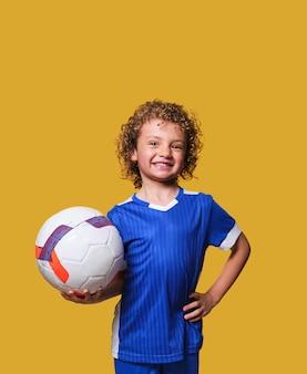 라틴계 소년 축구 선수 격리 된 벽에 공을 보유