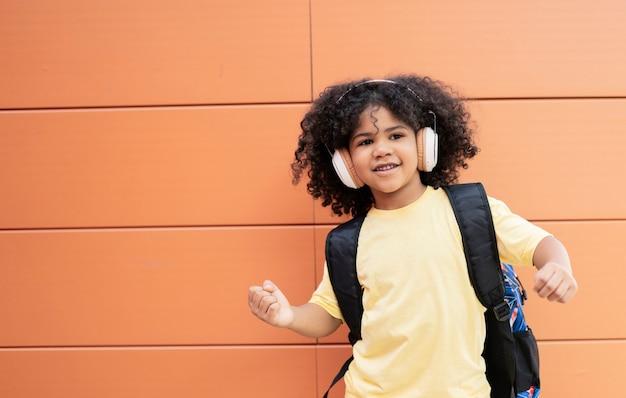 カメラを見ながらヘッドフォンとバックパックを身に着けているラテン系の少年