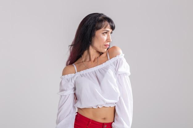 라틴 댄스, 즉흥 연주, 현대적이고 유행하는 댄스 개념 - 흰색 스튜디오 배경에서 춤추는 젊은 아름다운 여성