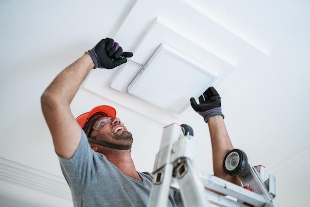 天井にledライトを設置するラテン系の電気技師。