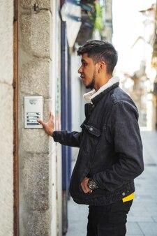 建物のドアベルを鳴らしているラテン系の男