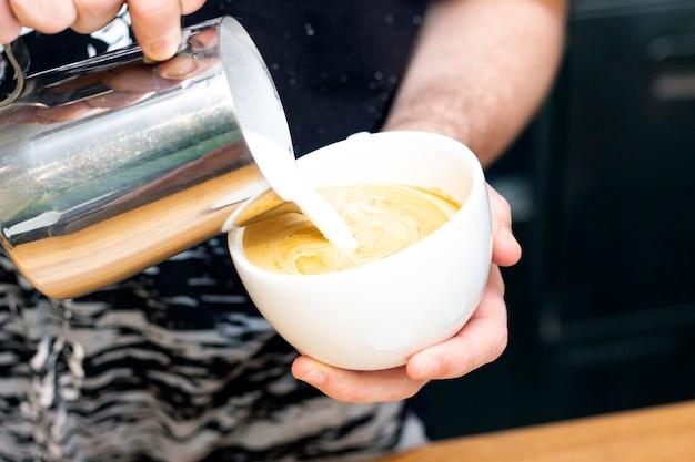 Латте-арт. искусство рисования на кофе. бариста делает молоко для латте-арт из кувшина
