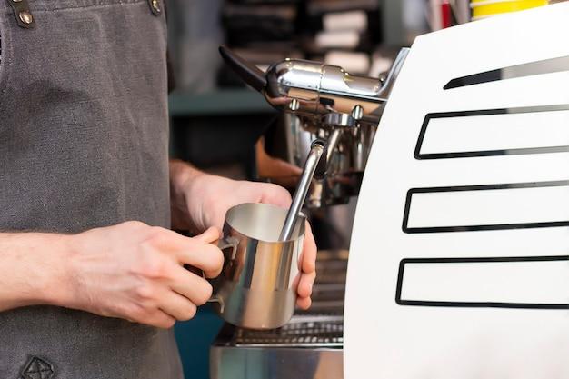 Латте-арт. искусство рисования на кофе. бариста взбивает молоко в кувшине паром из кофемашины