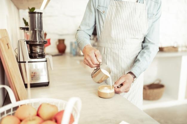 ラテアート。カウンターの近くに立っているバリスタが、小さなカップのカプチーノに泡立てたミルクを注いでいます。