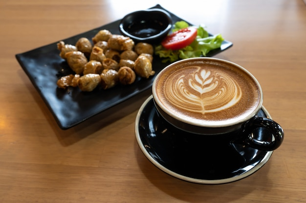 Latte art in black cup with snack on wooden table