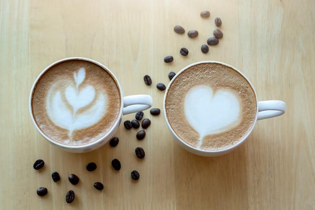 햇빛 아침 시간에 라떼 아트 커피와 커피 콩