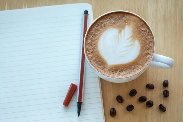 라떼 아트 커피와 햇빛에 아침 시간에 종이 노트와 볶은 커피 콩