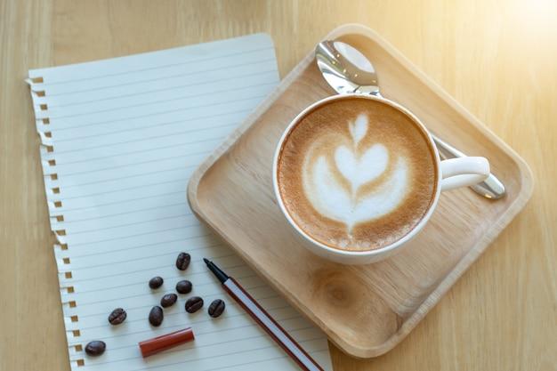 아침 시간에 종이 노트와 라떼 아트 커피와 볶은 커피 콩
