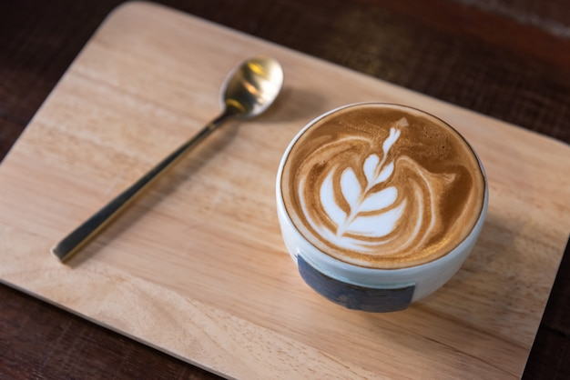 Latte art coffee cup heart shape topping and spoon on wooden plate