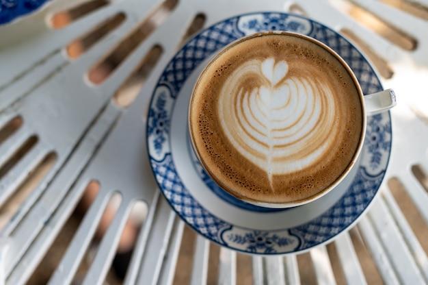 Кофейная чашка искусства латте на столе. плоская планировка