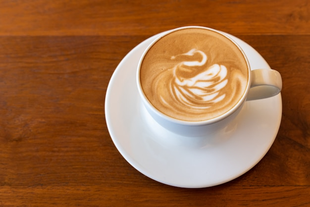 Latte art coffee cup swan shape topping on wooden table