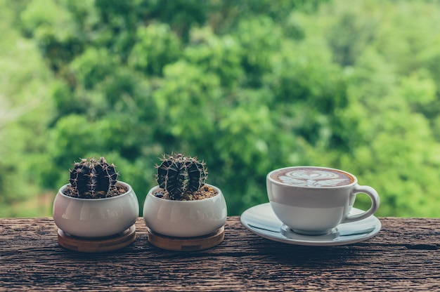 Latte art coffee cup with cactus pots on wooden table