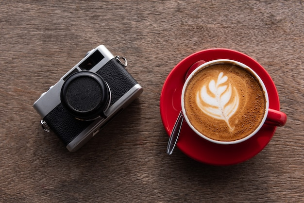 Latte art coffee and film camera on wooden table, top view
