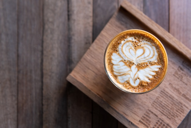 Latte art coffee in glass cup on wooden plate and wooden table, top view