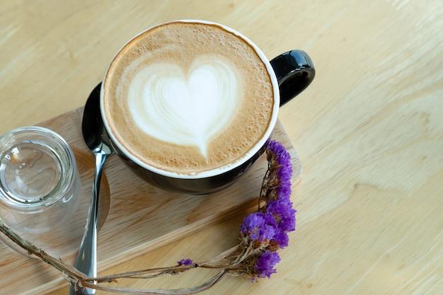 테이블 나무 배경에 햇빛 아침 시간에 라 떼 아트 커피.