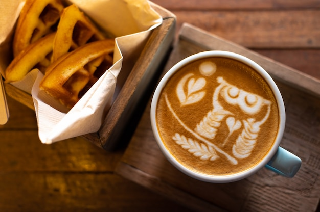 Latte art coffee with waffles on wooden table