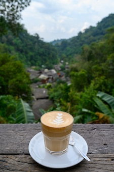 Latte art coffee on wooden table at chom nok chom mai at mae kam pong, chiang mai, thailand Premium Photo