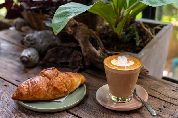 Latte art and croissant  on rustic wooden table