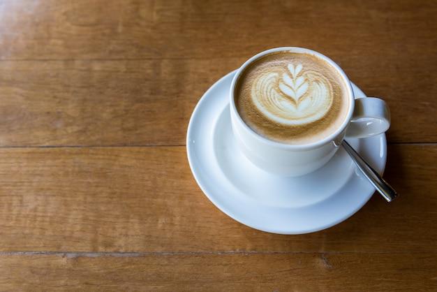 Latte art (heart shape) on wooden table