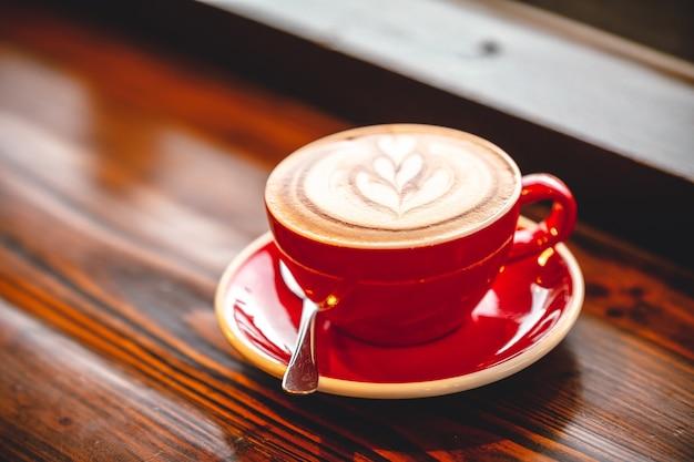 朝の木製テーブルの上のラテアートホットコーヒー
