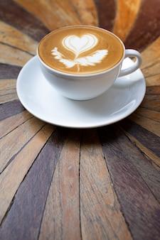 Латте-арт в белой кофейной кружке на деревянном столе