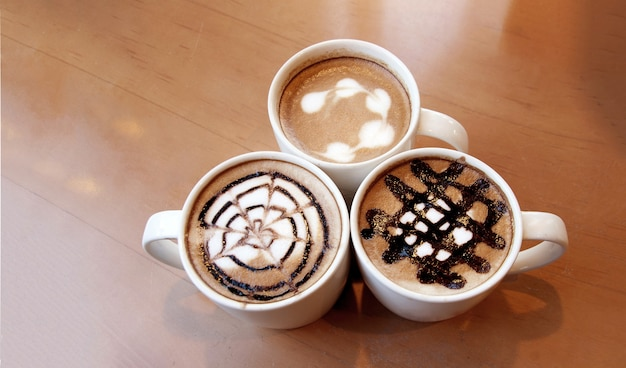 Латте-арт на кофейной чашке на деревянном столе