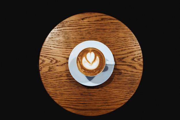 Latte art on wooden table vector