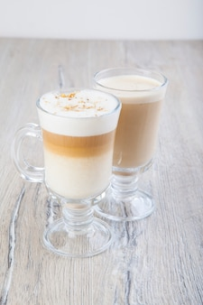 Latte cappuccino in a transparent glass on a jar background