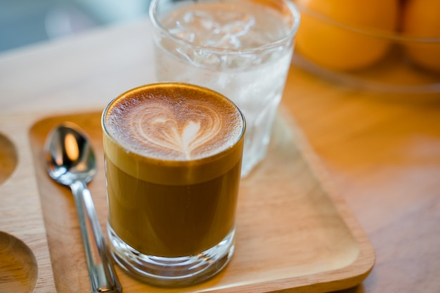 Latte coffee art served with a glass of water