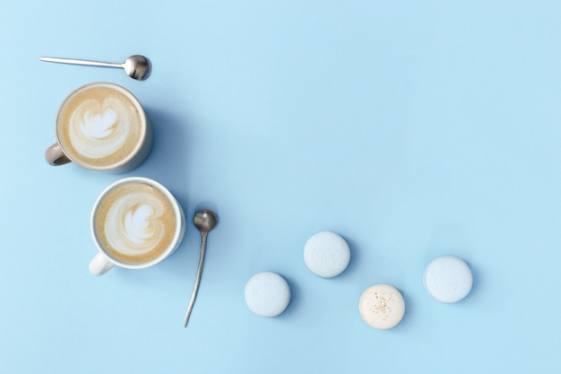 Latte coffee art in two big mug and sweet macaroons on gentle blue colored background. morning hot beverage and dessert for couple of people. flat lay.