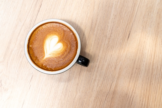 Latte coffee or cappuccino coffee in black cup with beautiful heart latte art on wooden table.