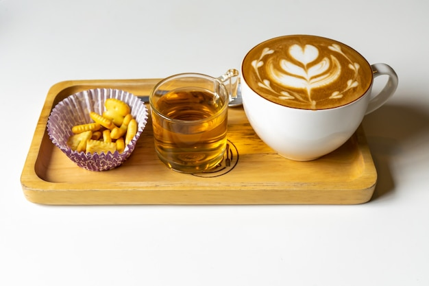 Latte coffee or cappuccino coffee in white cup with beautiful tree heart latte art on wooden table.