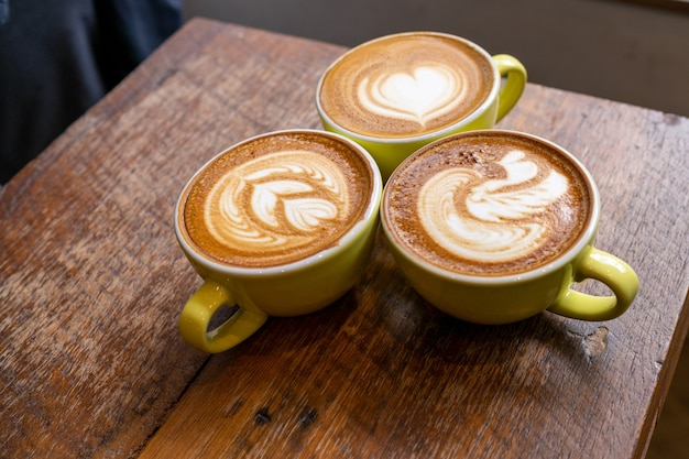 Latte coffee or cappuccino coffee in white cup with beautiful tree latte art on wooden table.