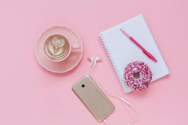 ラテコーヒーカップ、振りかけるおいしいピンクドーナツ、ノートとペン、イヤホン付きスマートフォン