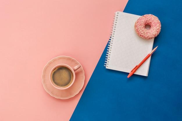 ラテコーヒーカップ、振りかけるおいしいピンクドーナツ、ノートとペンのノート