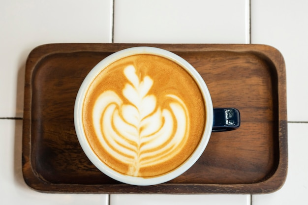 Latte coffee in a cup on wood tray