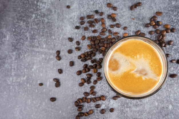 Latte coffee in a glass with cream on gray background with scattering of coffee beans.