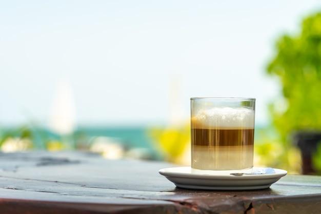 海と空の背景と木製のテーブルの上のガラスのラテコーヒー。