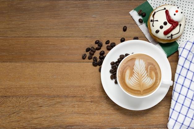 나무 테이블에 라떼 커피 또는 카푸치노 커피와 크리스마스 도넛