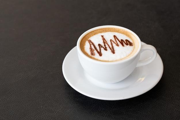 ラテアートと白いカップのラテコーヒーまたはカプチーノコーヒー