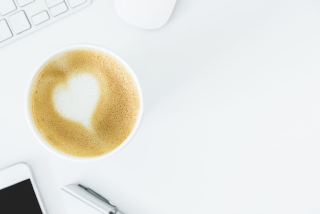 A latte coffee with art heart milk on the white desk table from top view and copy space. flat lay with desk, business and valentine concept.