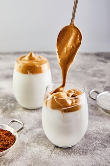 背の高いグラスとミルクのコーヒーフォーム入りラテエスプレッソ