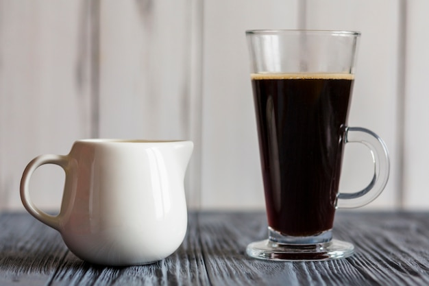 Latte glass with dark coffee and pitcher
