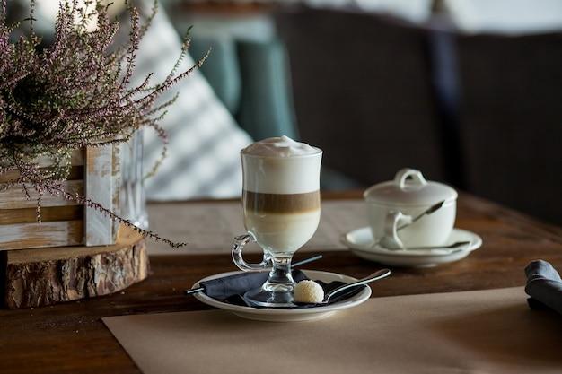 쿠키, 지팡이 설탕을 제공하는 나무 테이블에 맛있는 거품 투명 유리와 라떼 마끼아또 커피.