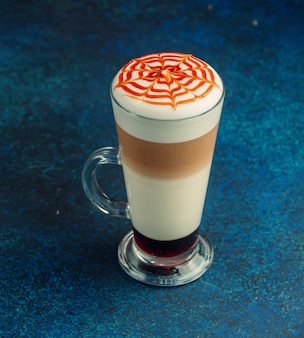 Latte macchiato with whipped cream and caramel strips on top