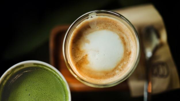 Крупный план горячего кофе latte и чая matcha зеленого в чашке на таблице. вид сверху. кафе или ресторан сцена