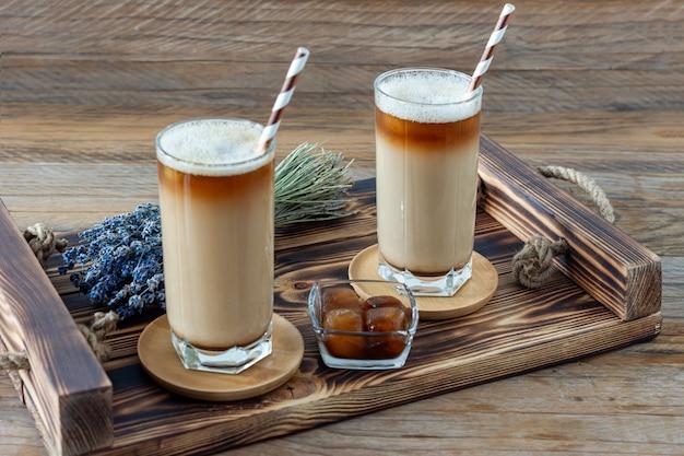 木製トレイの背の高いガラスにミルクフォームとラベンダーを添えたラテまたはカプチーノ。