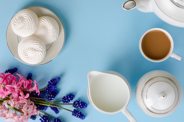 Latte, white meringues, milk jar on pastel blue background decorated with muscari and hyacinth flowers.